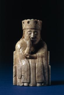 A queen from the Lewis Chess set sitting on a throne with her head in her hand
