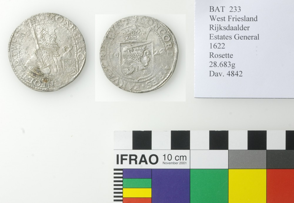 Two sides of a silver coin recovered from the Batavia Shipwreck placed next to a standard colour guide