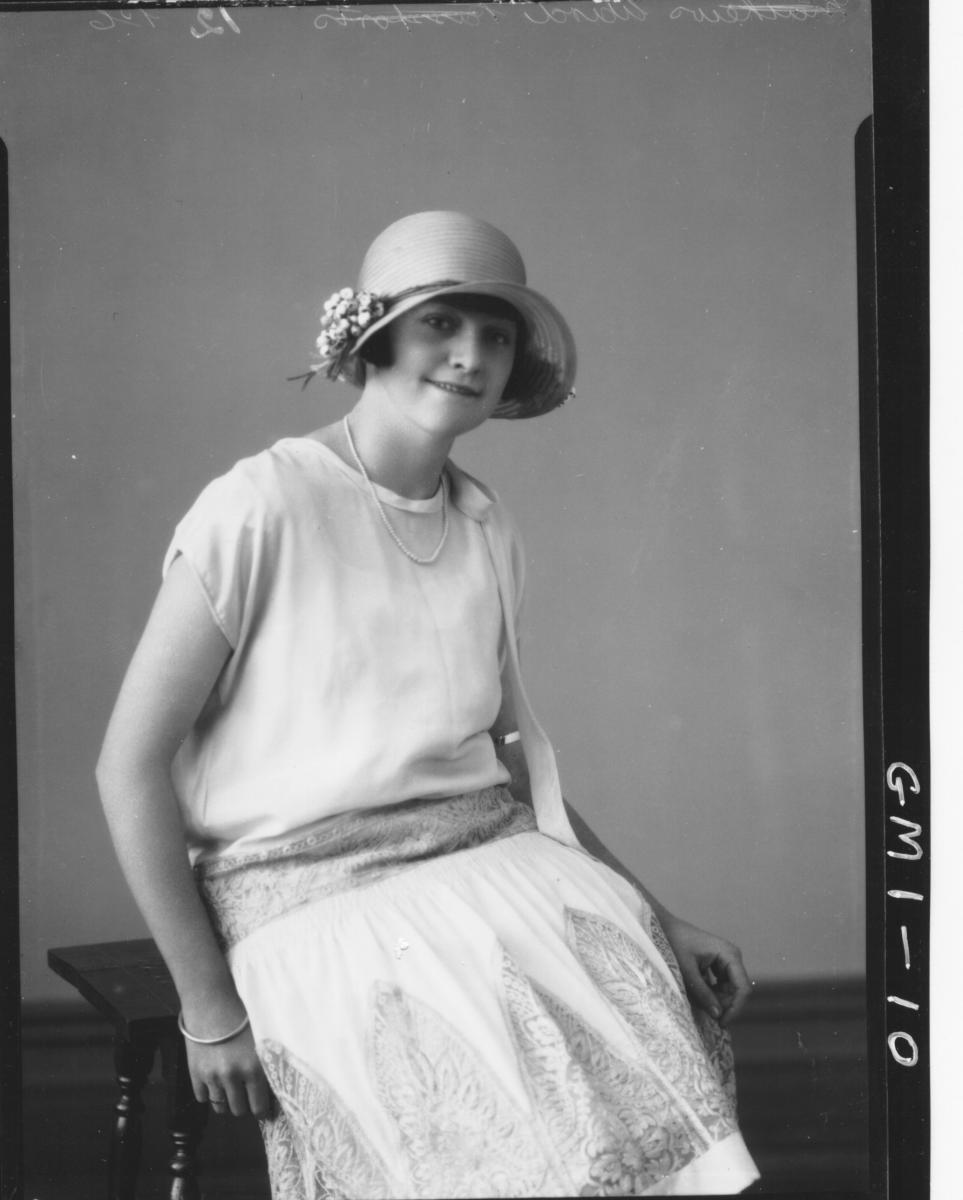 Portrait of a young woman seated short sleeve dress and hat, 3/4,'Wird?'.
