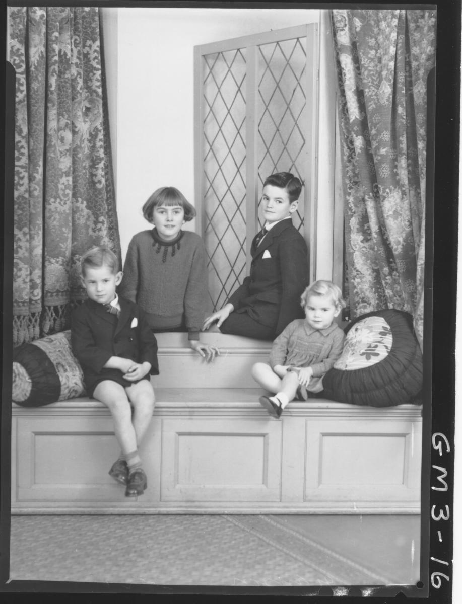 Portrait of two young boys in suits and two young girls in dresses. in window seat setting in studio, F/L,'Johnson'.