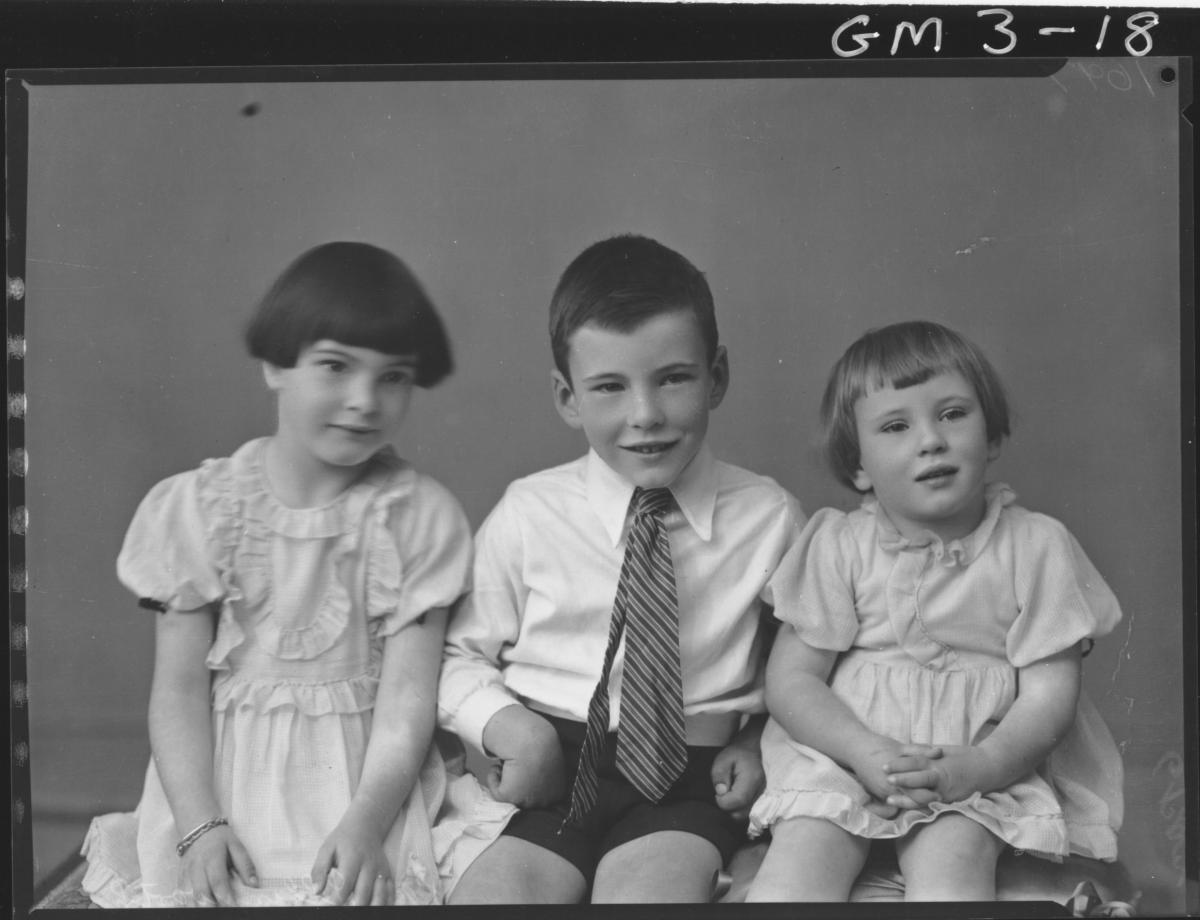 portrait of two young girls in dresses and young boy in shirt and tie, sitting on cushioned bench, 3/4,'Illingworth'.