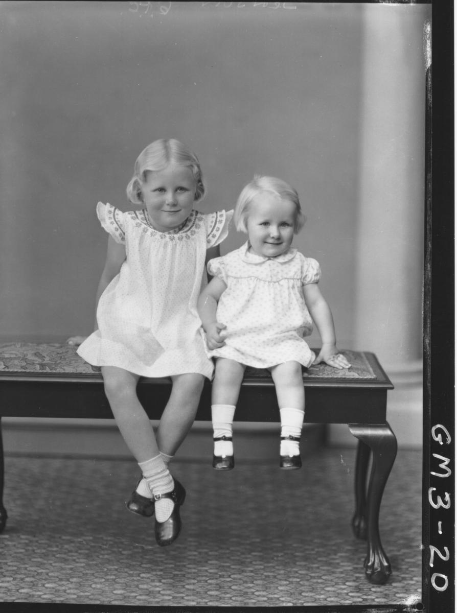 Portrait of two young girls, F/L, 'Jenson'. In dresses, sitting on cushioned bench.