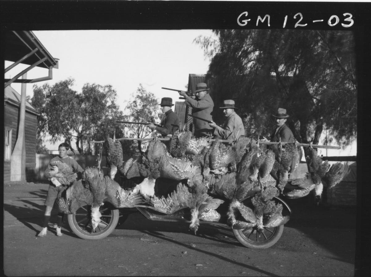 Five men with guns showing off their Wild Turkey catch, 'Duff'