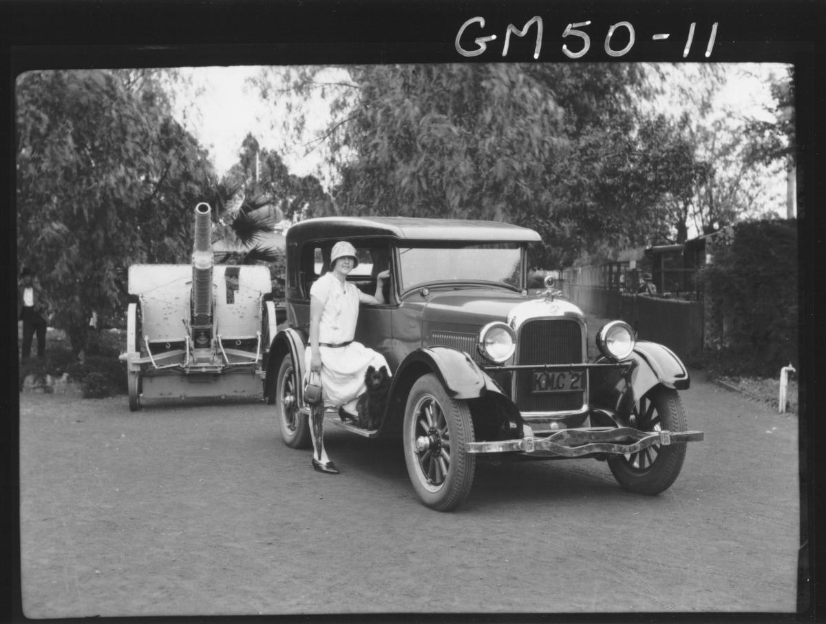 Miss Goldfields beside car in park large gun in background, Churack