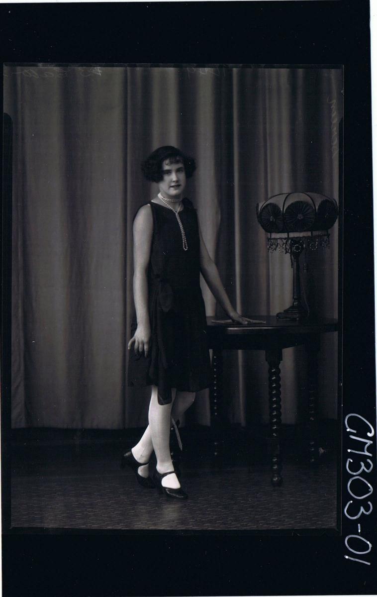 F/L Portrait of woman standing, wearing knee length dress; 'Screen'
