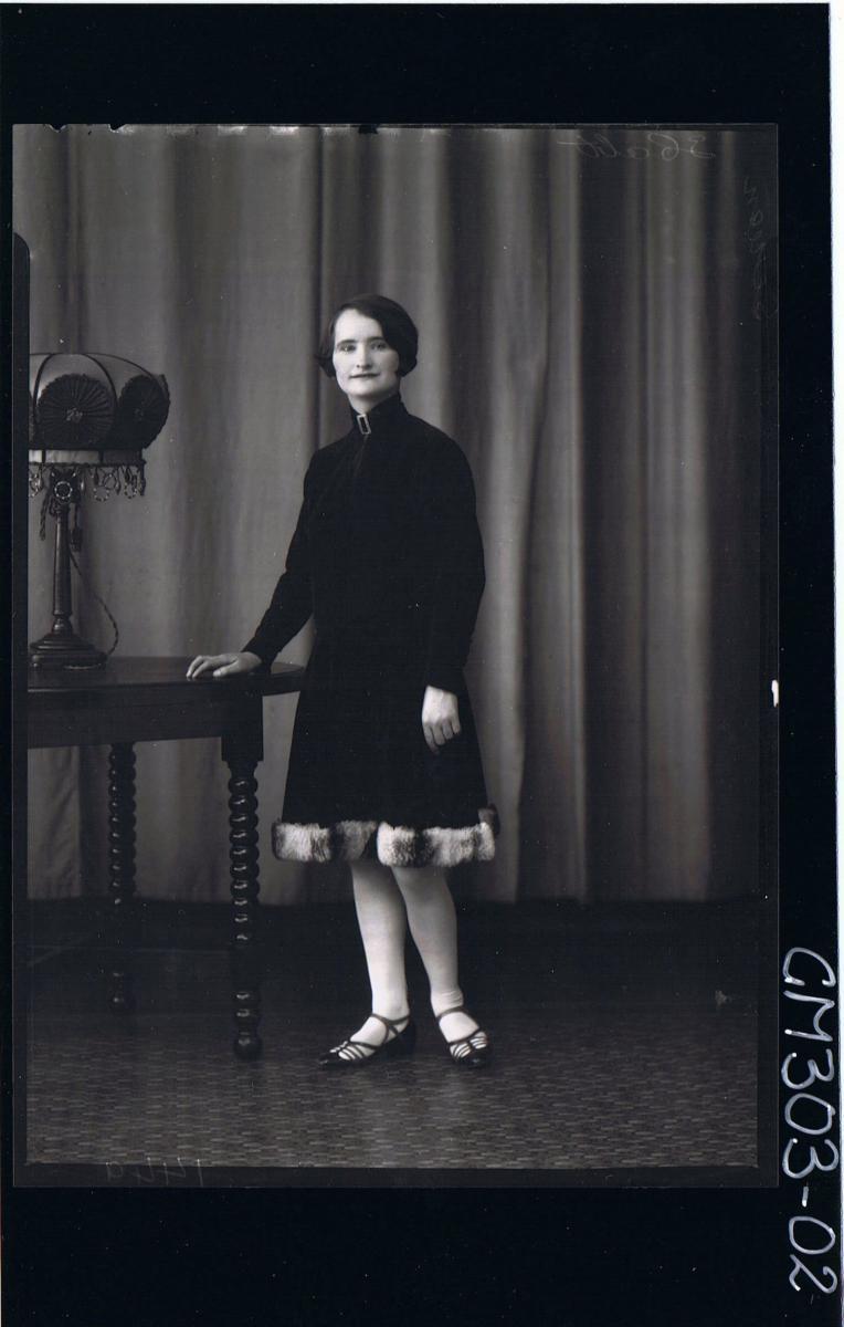 F/L Portrait of woman standing, wearing knee length velvet dress with fur hemline; 'Screen'