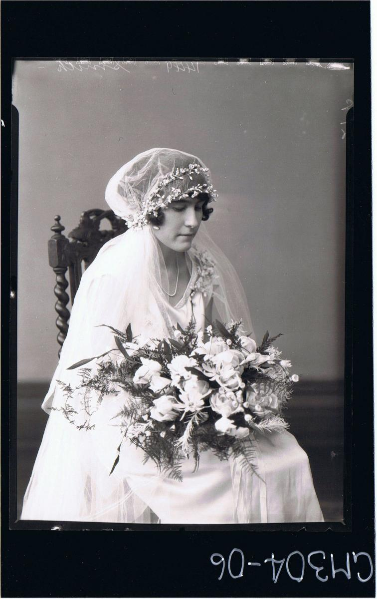 3/4 Portrait of woman seated wearing wedding dress, veil, holding bouquet of roses; 'Smith'