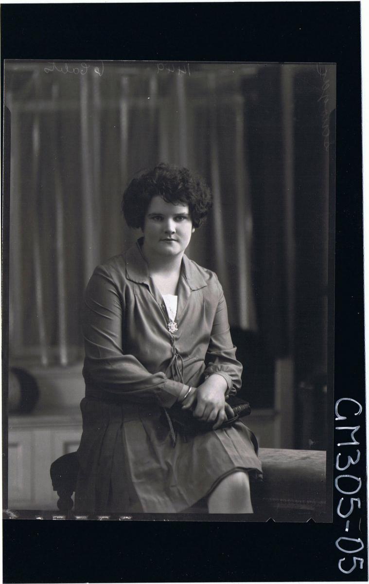3/4 Portrait of woman seated, wearing knee length dress, holding handbag; 'Scriuger'