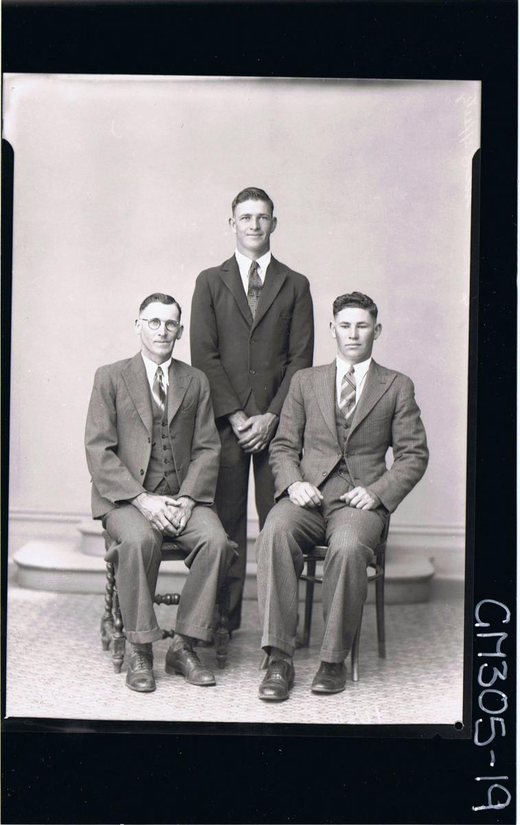 F/L Group Portrait of two men seated wearing three piece suits, one man standing; 'McCaffertey'