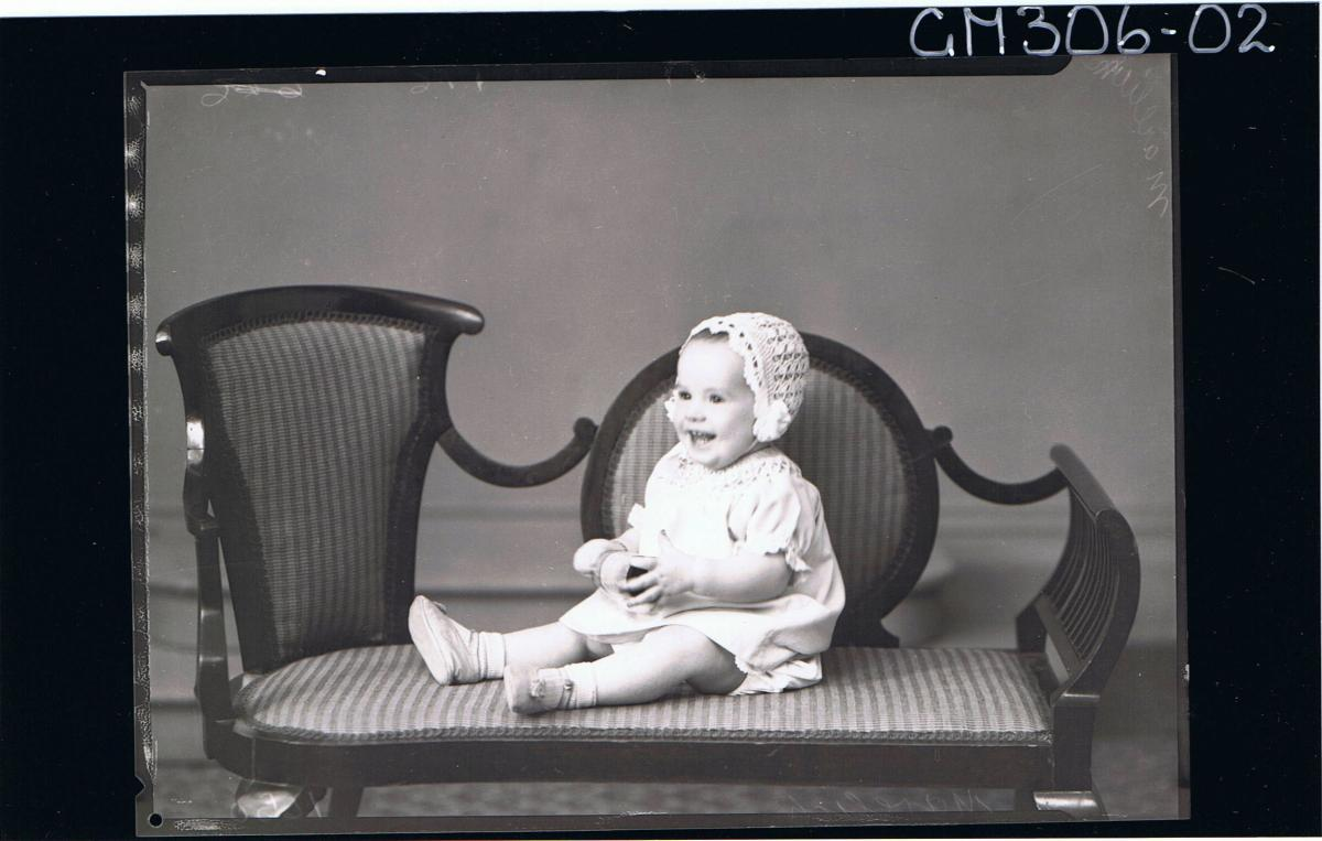 F/L Portrait of baby seated, wearing short dress and bonnet; 'Marelich'