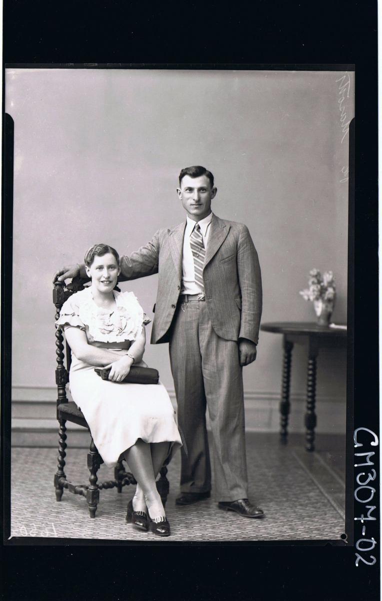 F/L Portrait of man standing wearing suit, woman seated wearing knee length dress, holding handbag; 'Masotti'
