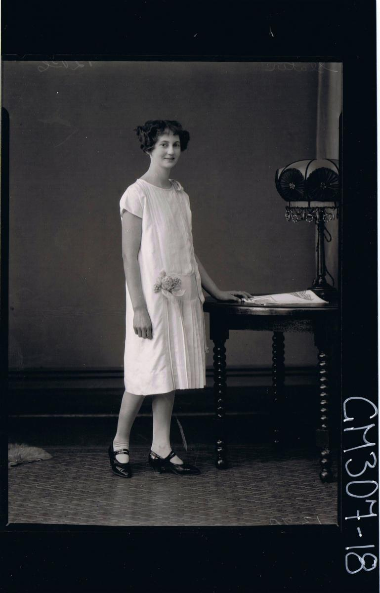 F/L Portrait of woman standing wearing knee length dress with pleats down front & flowers attached to side; 'Slater'