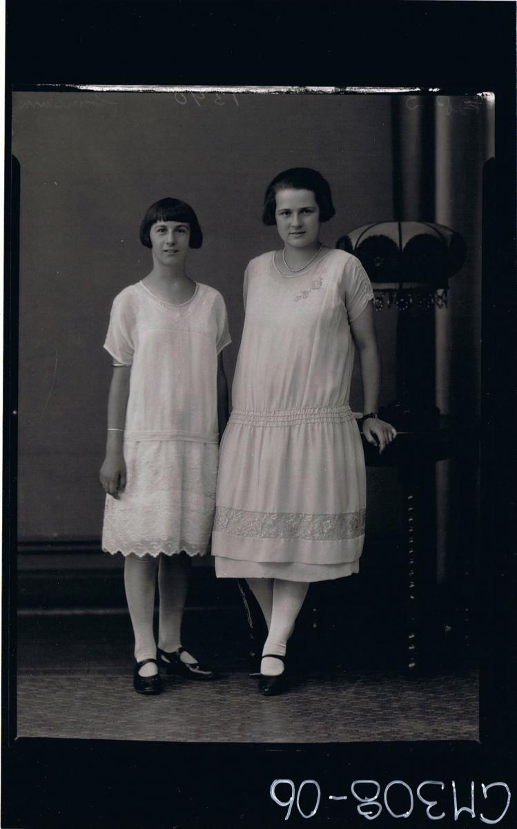 F/L Portrait of woman and teenage girl both standing, wearing knee length lace dresses; 'Sansum'