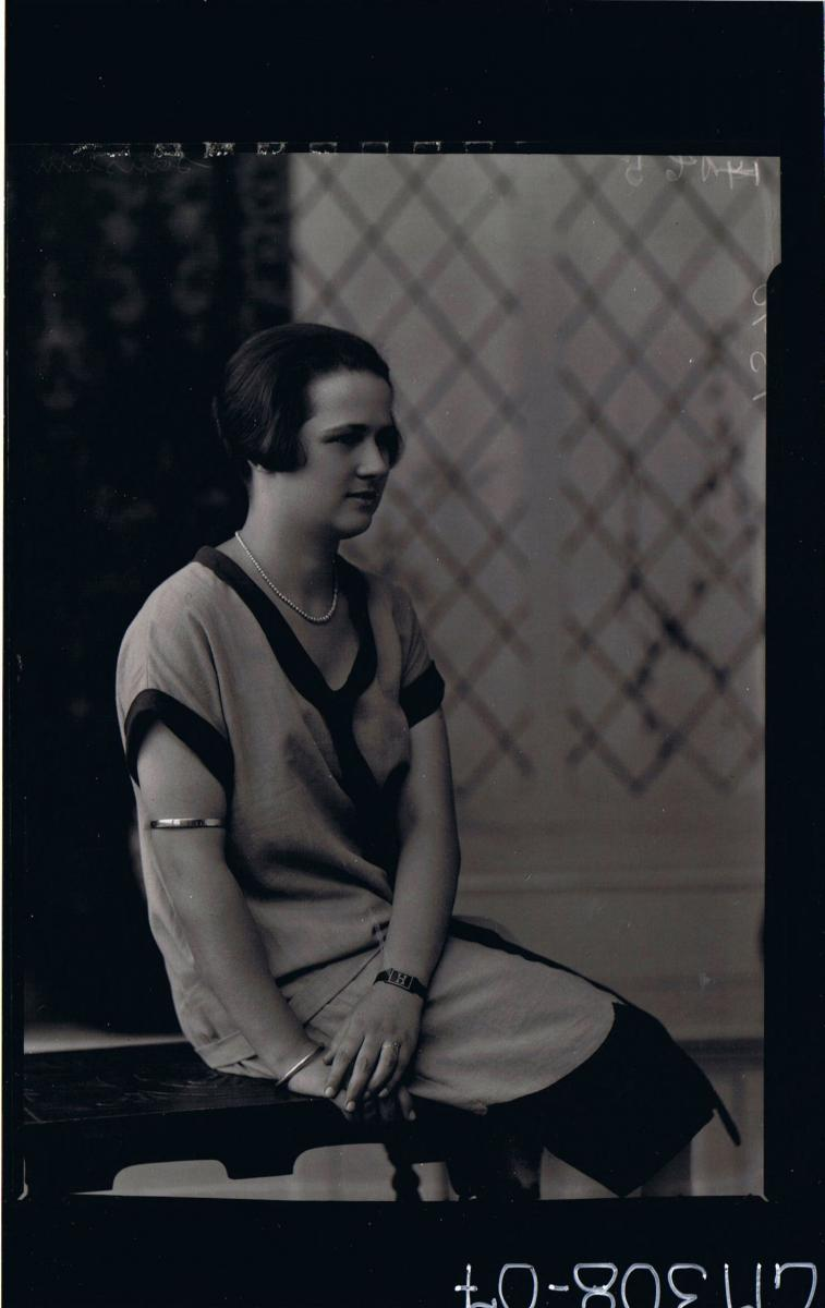 3/4 Portrait of woman, seated wearing knee length dress, strap with letter H round wrist; 'Sansum'