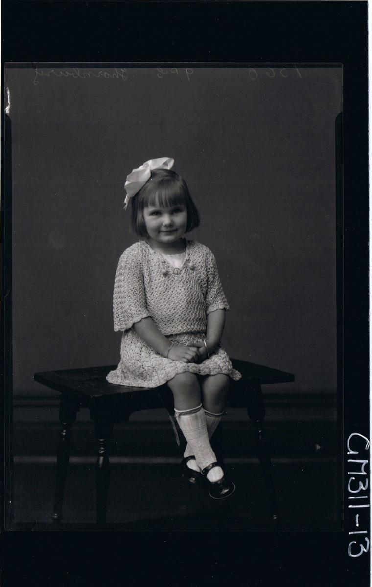F/L Portrait of girl seated wearing short crochet dress, ribbon in hair 'Thornbury'
