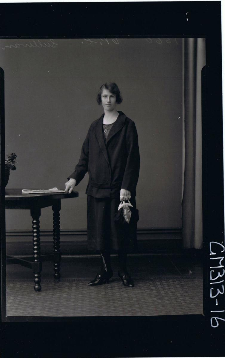 3/4 Portrait of woman seated,wearing three quarter length skirt and matching jacket,holding gloves & handbag 'Sullivan'