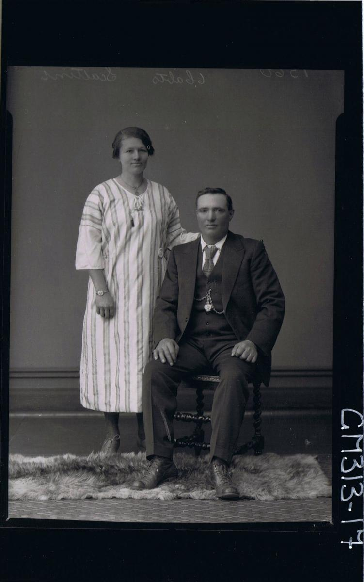 F/L Portrait of man seated wearing 3 piece suit, woman standing wearing 3/4 length striped day dress 'Scattini'