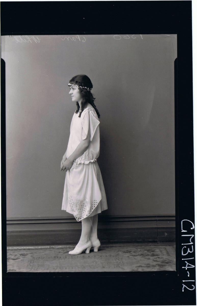 F/L Portrait of young woman standing wearing knee length evening dress, (side view) 'White'