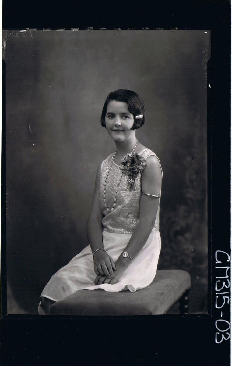 3/4 Portrait of woman seated, wearing satin knee length dress corsage on shoulder 'Mitchell'