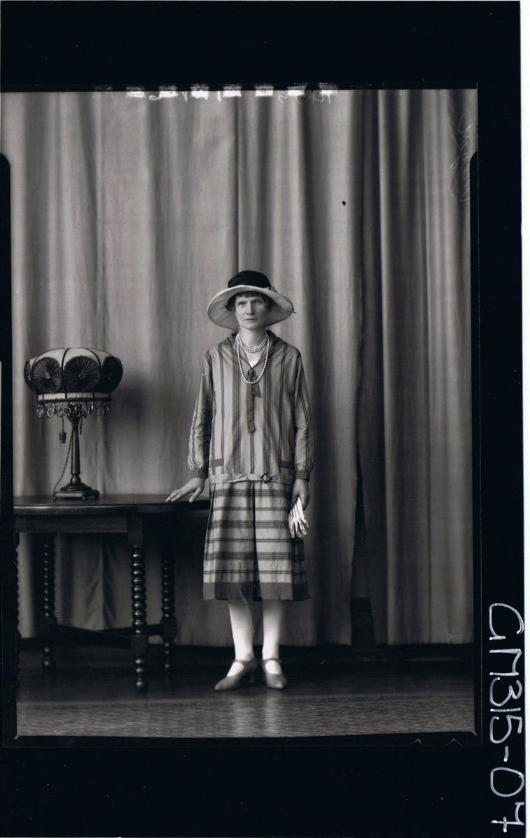 F/L Portrait of woman standing wearing 3/4 length striped day dress and hat, holding gloves 'Meyer'