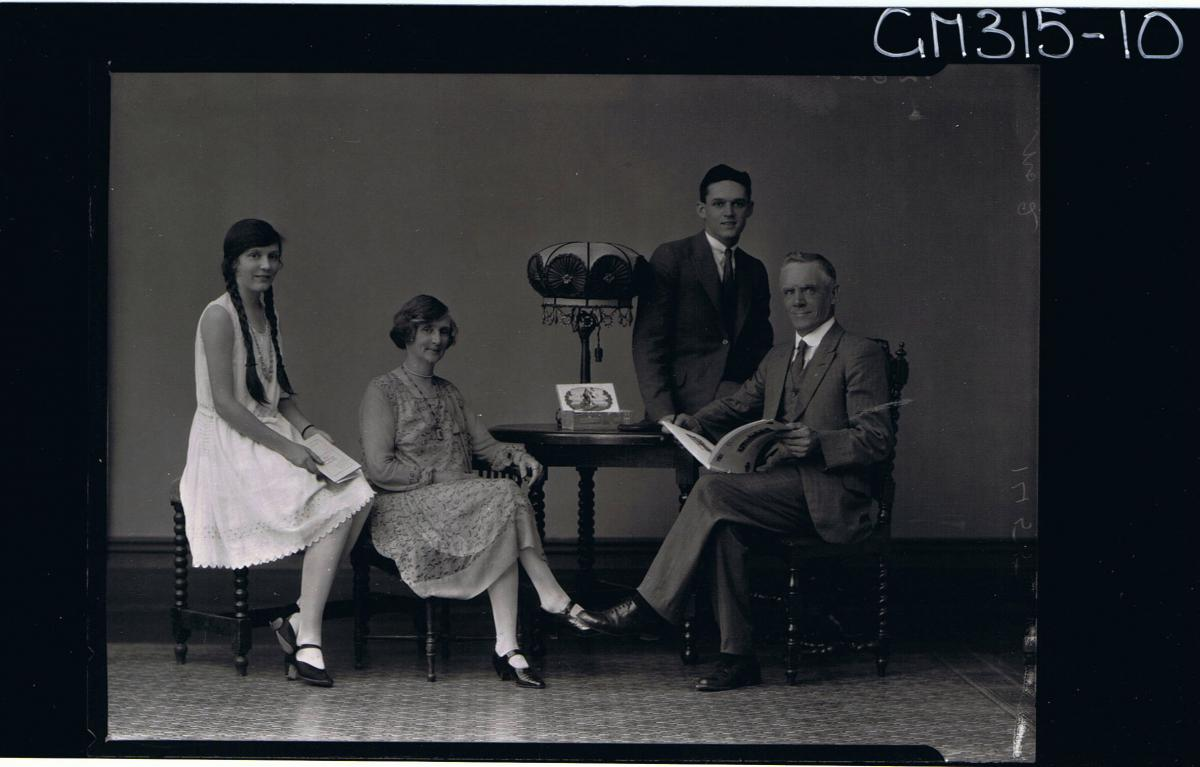 F/L Family Portrait of a man and woman seated, man holding a book, young woman and young man seated on table 'Murray'