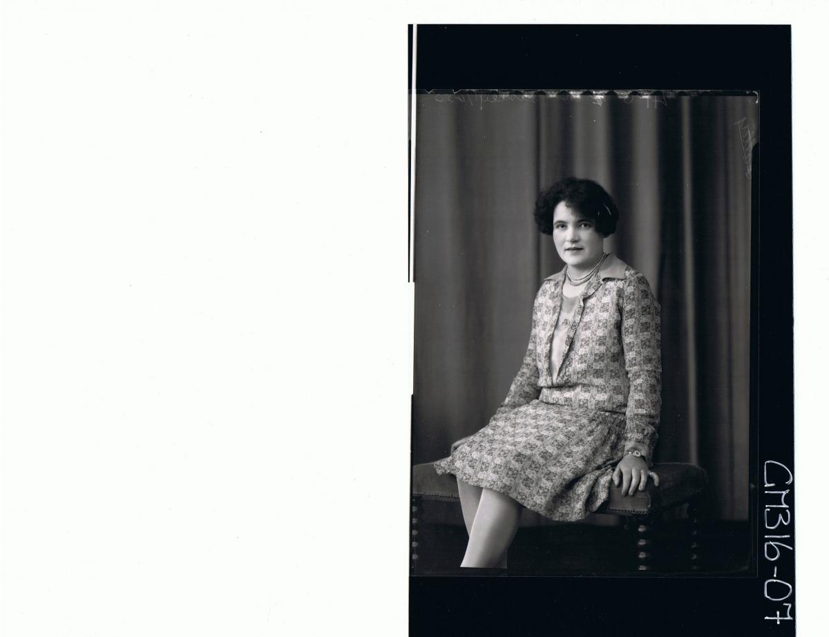 3/4 Portrait of woman seated wearing knee length patterned dress 'Kinely'