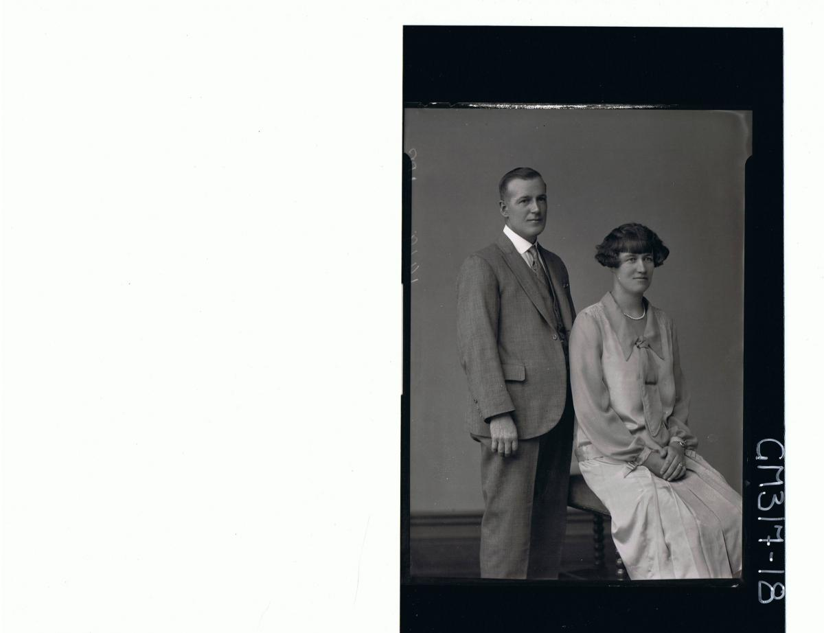 3/4 Portrait of man standing wearing three piece suit, woman seated wearing dress with pleats and tie; 'Morrow'