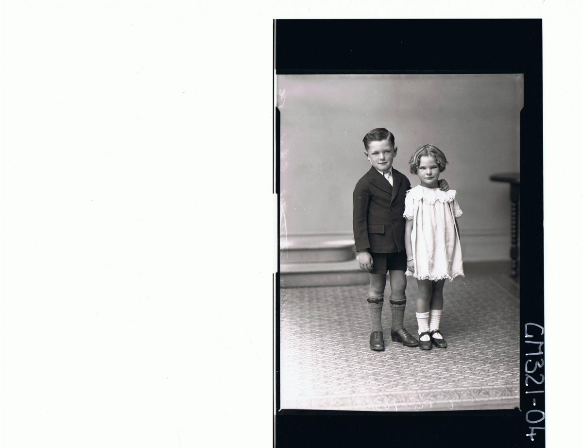 F/L Portrait of boy standing wearing shorts, shirt, tie, jacket, girl standing wearing short lace dress; 'Mullins'