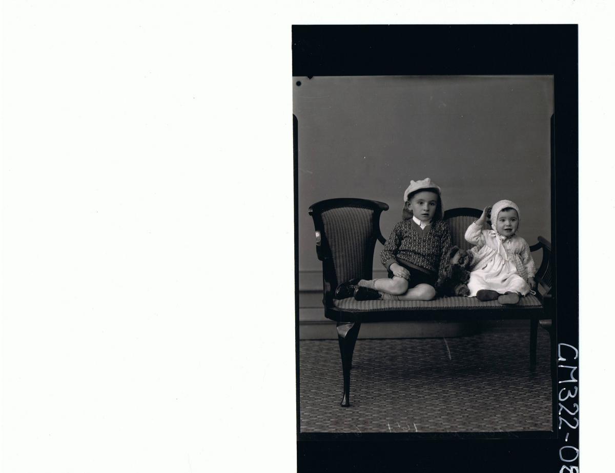 F/L Portrait of boy seated, wearing shorts, jumper, baby seated wearing dress & cardigan, koala between them; 'Moylan'