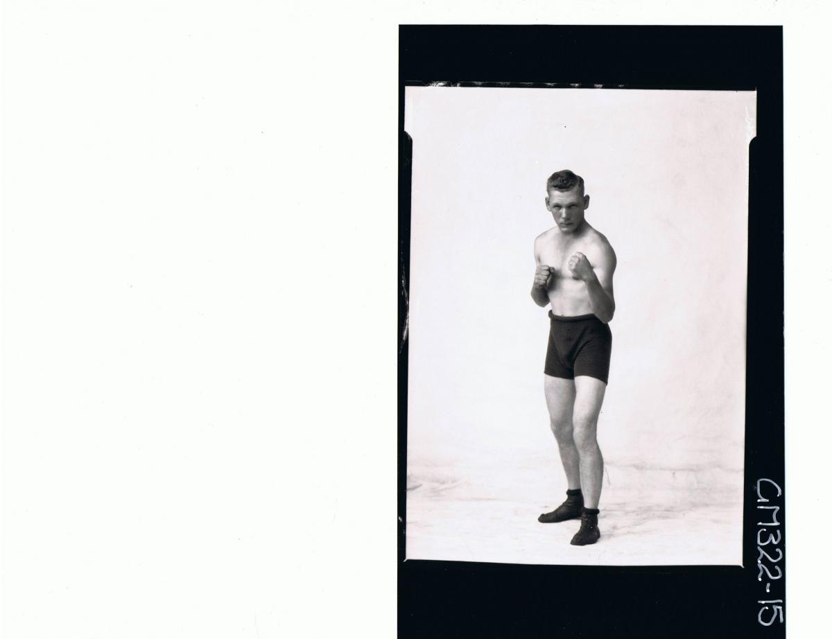 F/L Portrait of man standing in boxing position, wearing boxing shorts and shoes; 'Trembath'