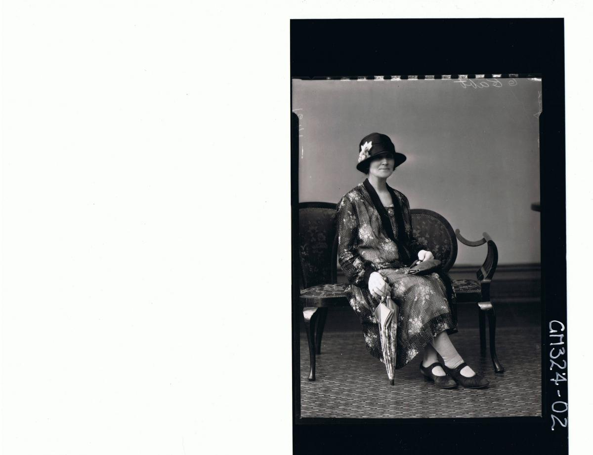 F/L Portrait of woman seated wearing 3/4 length floral dress, hat, gloves holding a handbag and umbrella; 'Stringbek'