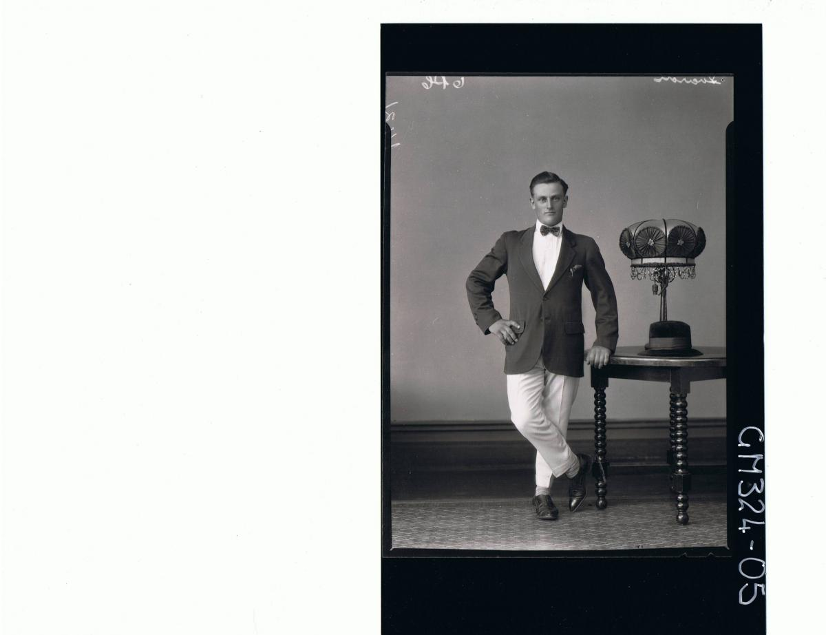 F/L Portrait of man standing wearing suit, hat on table; 'Luardi'