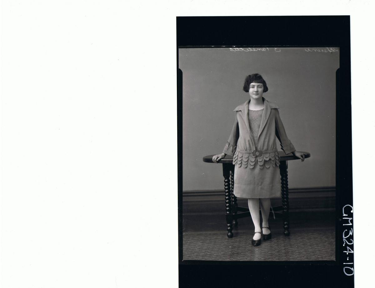 F/L Portrait of woman standing wearing knee length dress with matching jacket; 'Scherini'