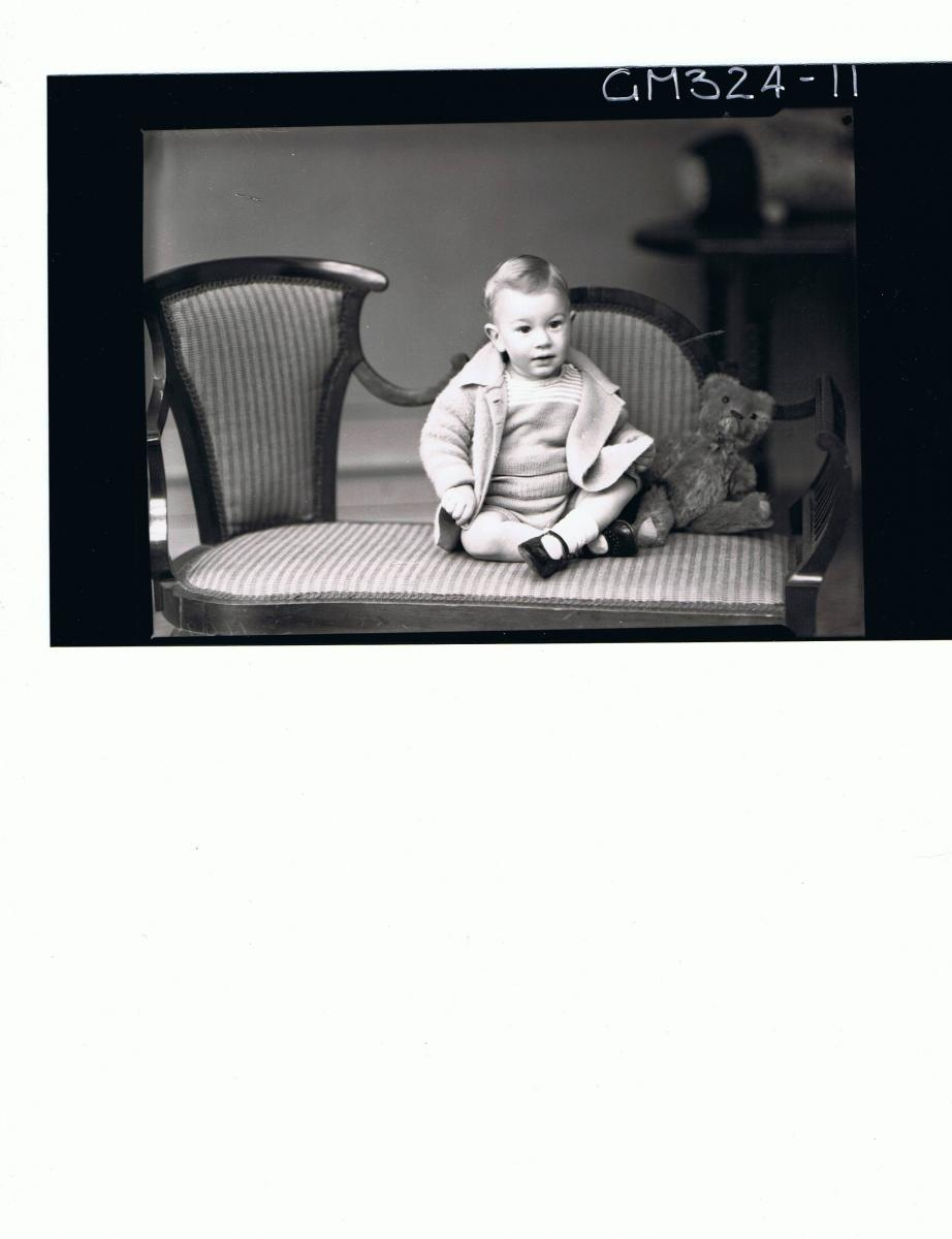 F/L Portrait of baby seated, wearing knitted shorts and top, jacket, teddy bear next to baby; 'Leggert'