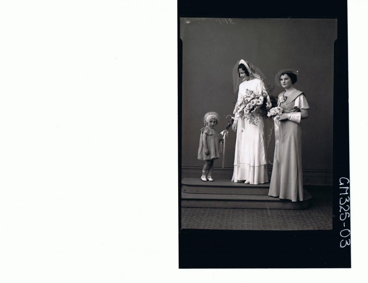 F/L wedding Portrait of bride standing wearing long dress, veil and gloves, holding bouquet, young woman & child 'Lynch'