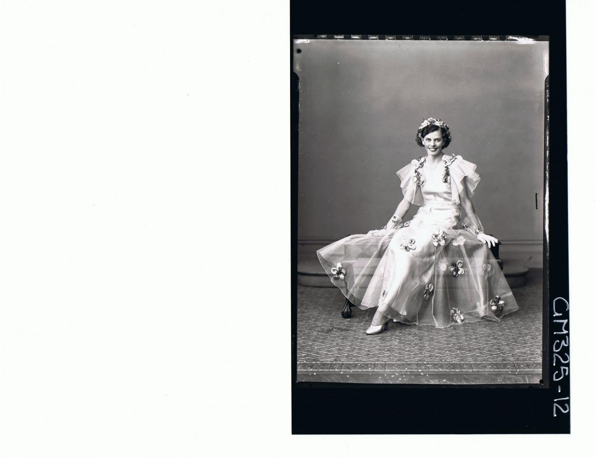 F/L Portrait of woman seated wearing long evening dress, with satin flowers attached, frilly sleeves, gloves, 'Lesque'