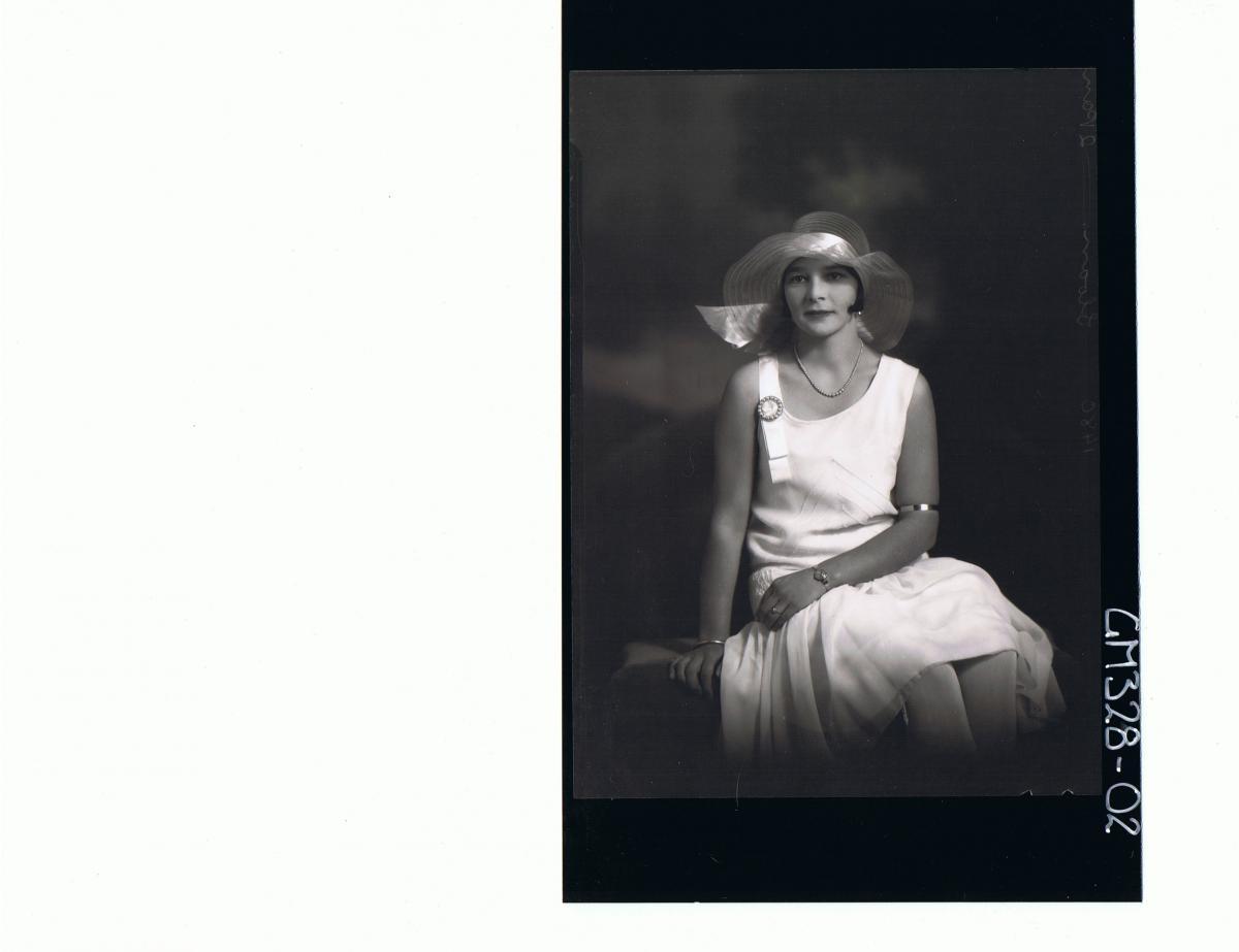 3/4 Portrait of woman seated wearing knee length dress, hat; 'Sloan'