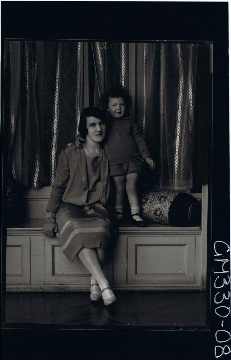 1/2 Portrait of woman seated wearing knee length day dress, male child standing,wearing knitted shorts & jumper; 'Maher'