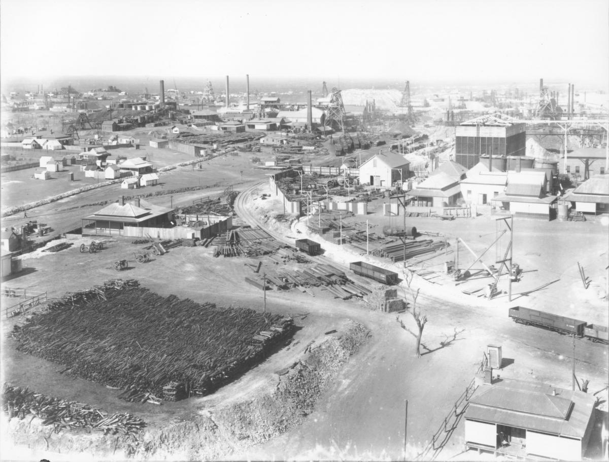 Panoramic view of Golden Mile and Boulder taken from Ivanhoe, large amount of mine timber in foreground, headframes and mine building.  EGHS neg BA.46  TSGM plate 6.1.239 (part).  Taken from Ivanhoe (Drysdale headframe?)  Note Golden ? No. 3 headframe between distant chimneys.Gt Boulder mainshaft headframe (centre distance) with ladgerwood? towers for tailings stackings behind.  Golden horseshoe main shaft to right behind Ivanhoes brush water cooler - note timber pile left foreground (firewood).  1905