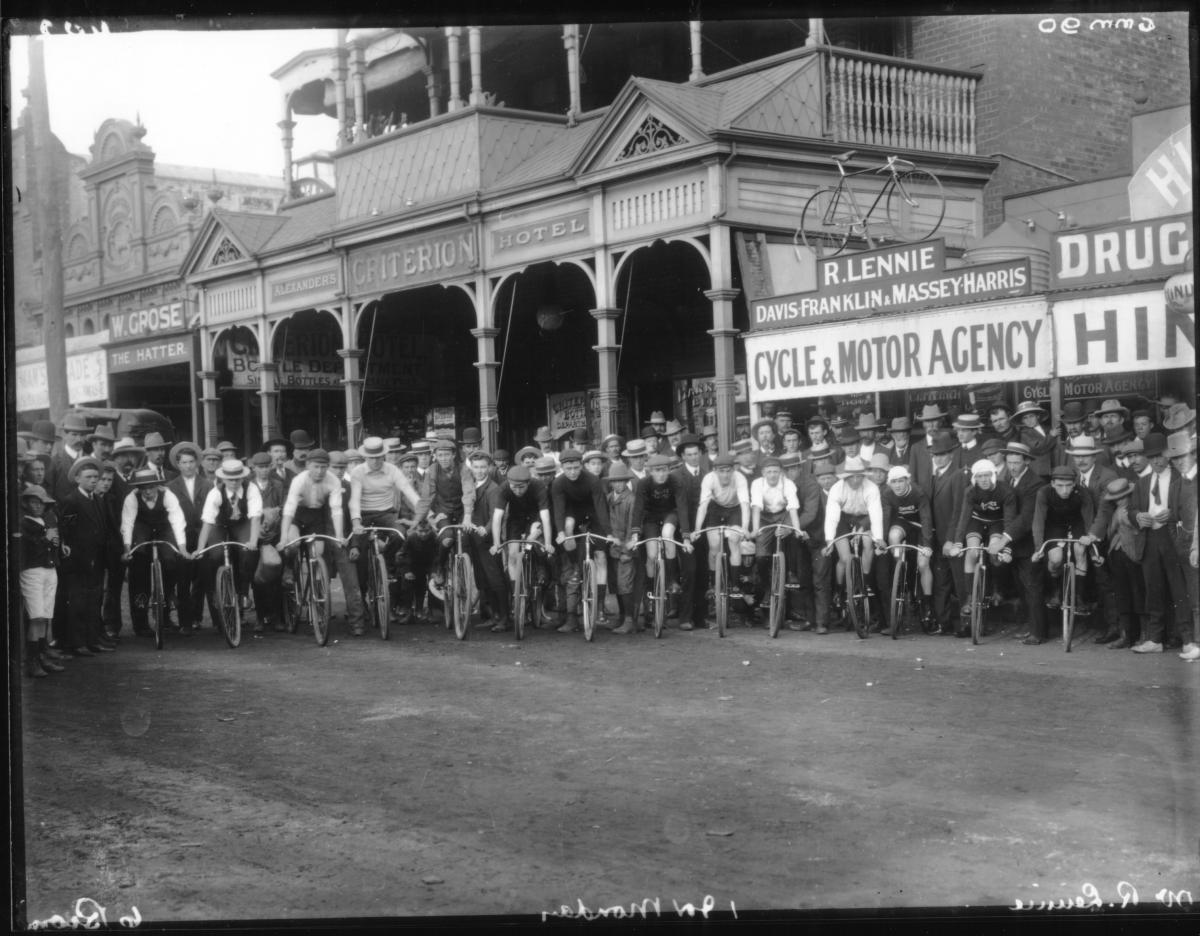 Large group of cyclists in Hannan Street outside Criterion Hotel and Mr. R. Lennie's Cycle Shop.  Large crowd watching start of road race.