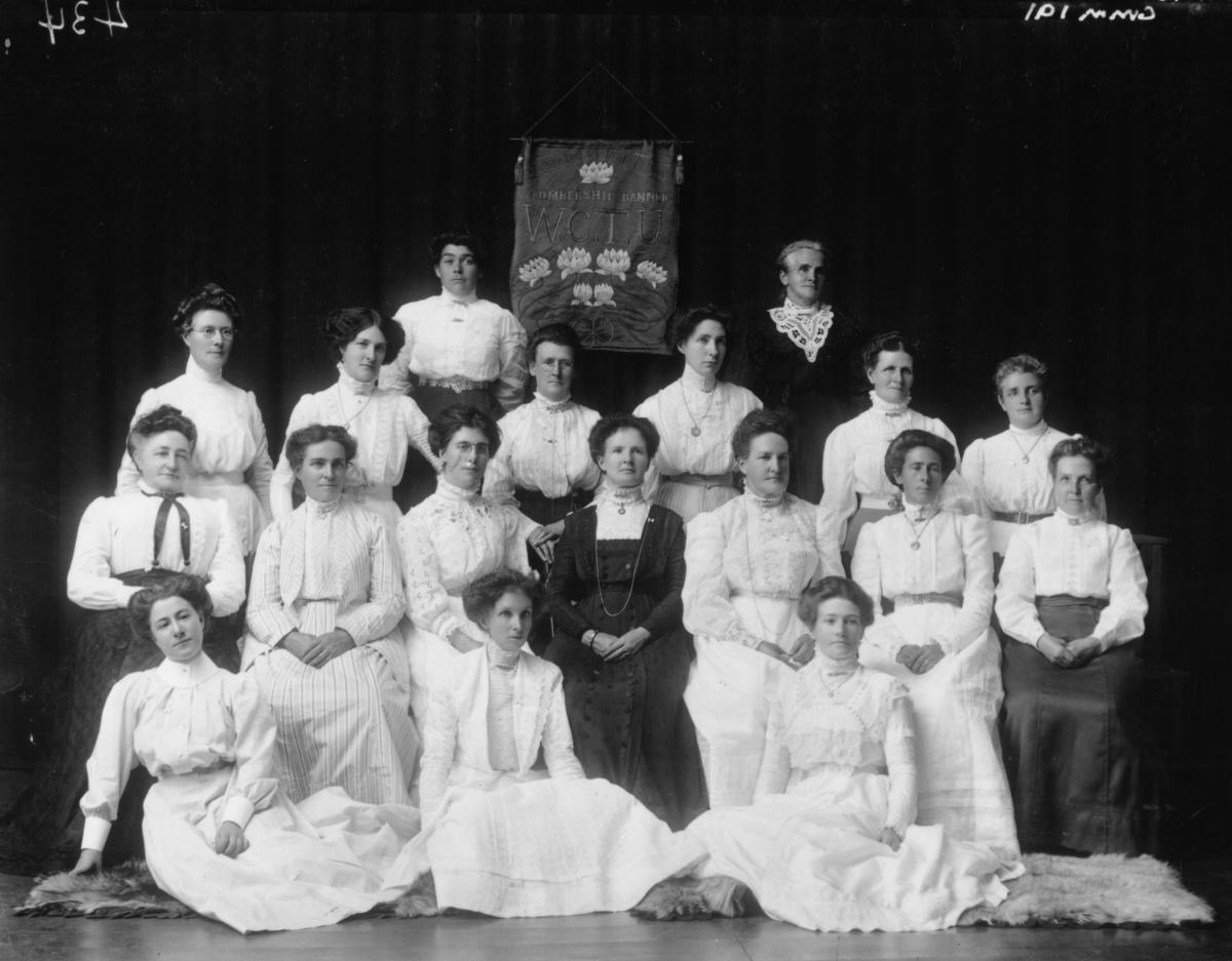 Group Portrait of Womens Christian Temperance Union Group. Mrs Annie Throssell presents banner to local W.C.T Group. Lady 2nd row from back far left: Sister Mildred Fairclough, 'Sister of the People' pioneer nussing sister 1896 trained in Adelaide.  Lady in centre in dark dress: Mrs Annie Throssell wife of George Throosell MLA & Comm of lands and who was sympathetic to womens causes.  Lady to right of Mrs Throssell Mrs R Hamilton wife of Richard Hamilton manager of Great Boulder Mine.  L:ady seated in...