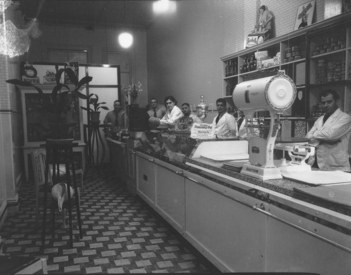 Interior of Kalaf's shop with footballPremiers Cup on counter donated by George Calaf.  Large CAYTON scales on counter, 'Bushells Tea' ad. on display with various other products in tins and jars. 1 woman and 5 men behind counter.