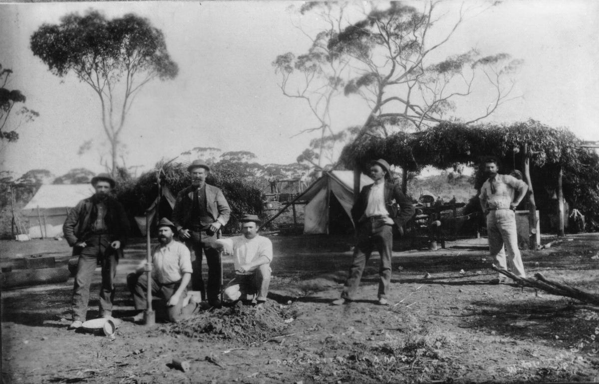 Early days mining camp. (for Mr. Reid.)  Alf Kyle's lease, 25 mile. Doncaster Camp.  C Mason, Col Cameron,kneeling,  standing L to R -  E Thheile, C Brown, Jerome de Jaries, Alf Kyle.  Tents and bush shelters in background.