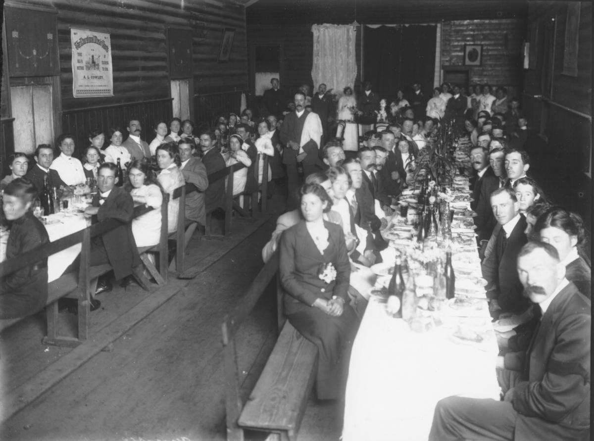 Wedding dinner party in hall with corrugated iron walls, wood dado.  Guests seated on benched at long tables set with cloths and food and drink. Window blinds have 'Adam' style decoration. Chart on left wall 'The Educational Music Chart- Set 1 - The Tonic Solfa method of teaching singing -A.L.Cowley.'