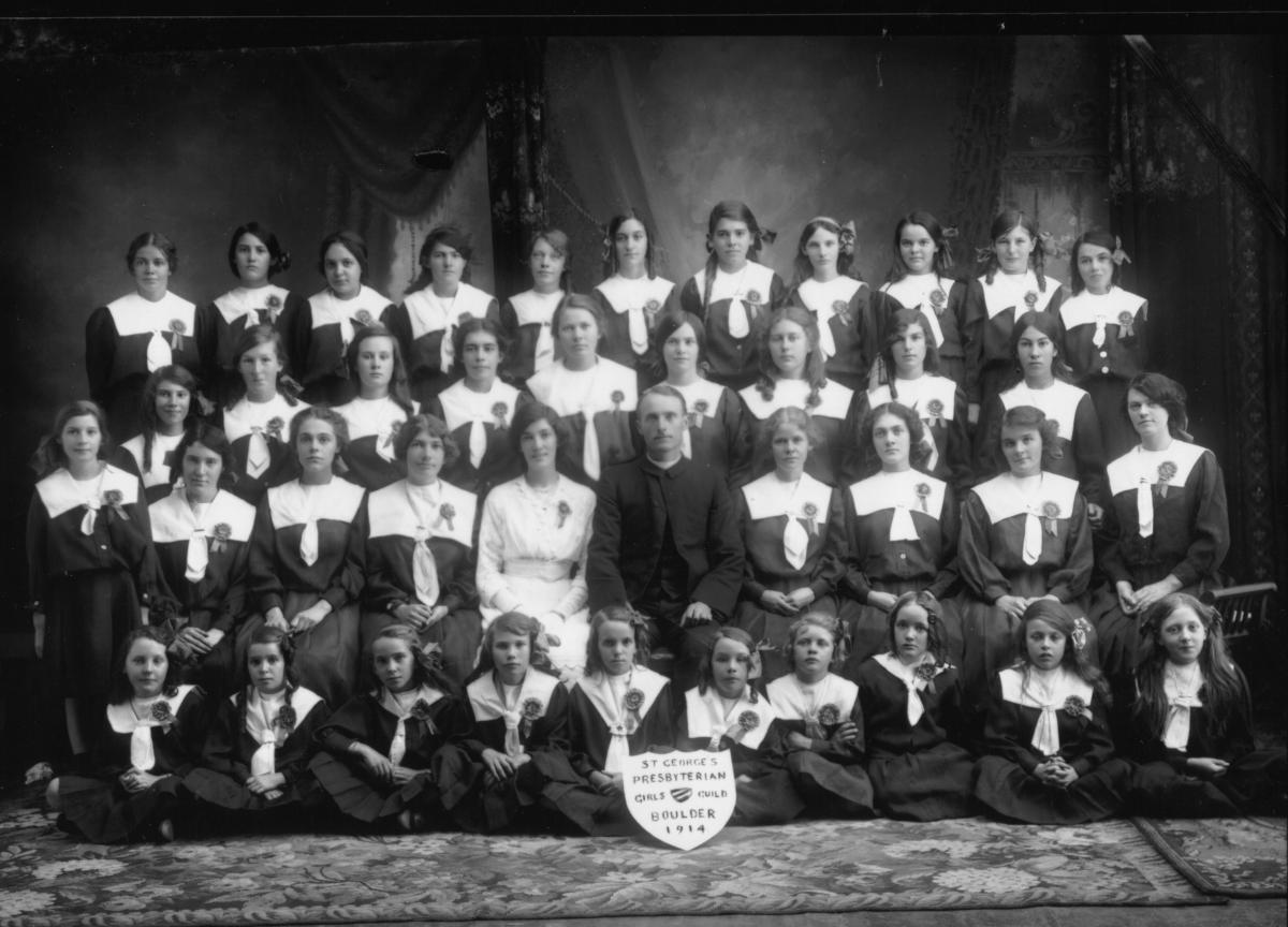 Studio group photograph of clergyman and girls wearing dark dresses with white sailor collars and rosettes. Shield inscribed 'St George's presbyterian Girls Guild Boulder 1914.