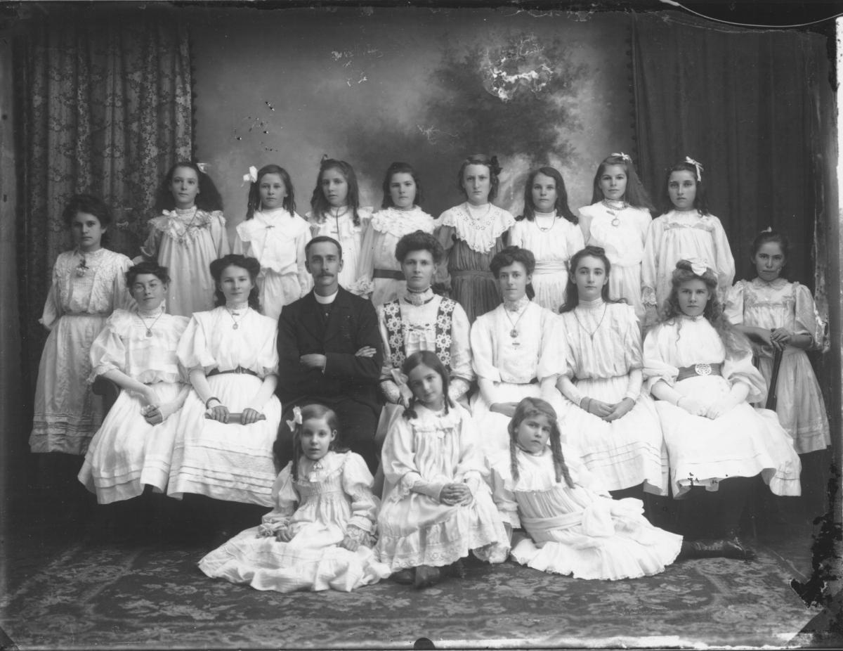 Group portrait of Minister and teacher with girls all wearing different dresses typical of the era. A Methodist group?   L>R (seated) Myra, Francis and her sister Alice (Both married 'Stearns') both possesed fine voices as soloists in Methodist choirs. Myra later married Ernest Stearne, had a family of four - Don, Barrie, Lesley and James. Barrie and Lesley still reside in Esperance on Lake Warden farm.  The' Stearnes Flats on the Esplanade c1930 (now the site of Bay of isles' luxury motel, near James St...