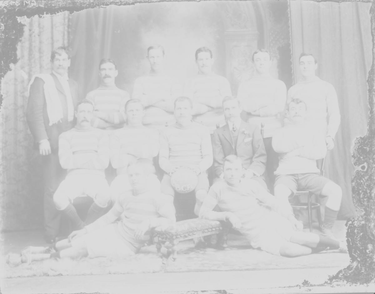 Group portrait of soccer team 'Premiers 1910 B.C.F.C.' written on ball.