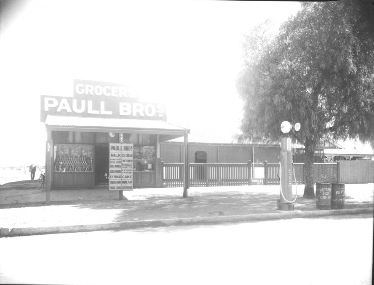 Paull Bros Grocery store, house attached, petrol pump on stree verge.  Advertising sign outside and large tree.