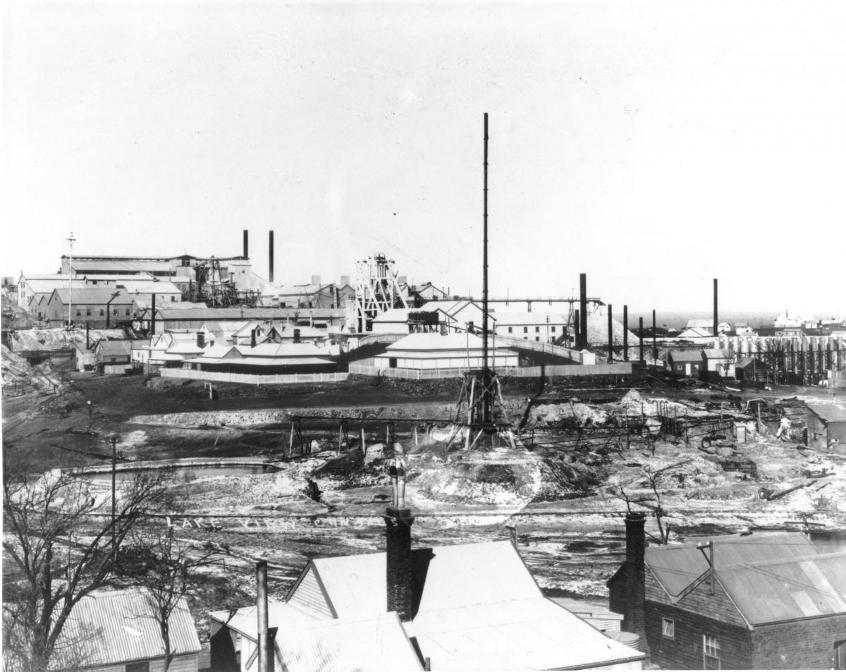 'Lake View Consuls'- corrugated iron rooms with brick chimneys in foregroundfenced from dry settling ponds, extensive mine buildings in background.