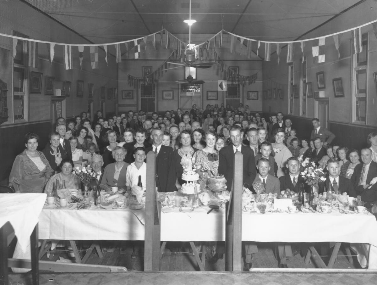 Large group of men, women children standing in hall by table set for wedding feast, 2 tiered celebration cake and other cakes on table with crockery, cutlery, drinks, flowers.Banners strung diagonally across room.